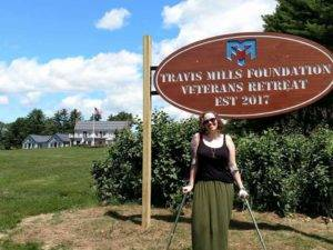 Shawna Barnes standing in front of the Travis Mills Foundation sign